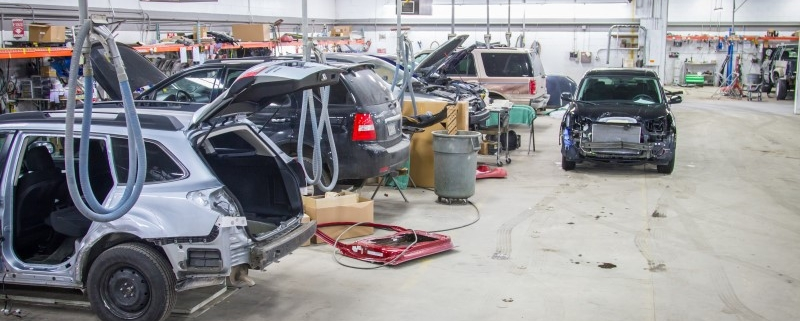 View of the interior of Peters Body Shop during the course of auto body repair. Six vehicles, from sedans to SUVs are pictured.